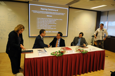 Joel Bertrand of CNRS, Lai Choy Heng of CQT,NUS, and Jorge Tredicce from University of Nice Sophia Antipolis shake hands after signing a research agreement at CQT on 9 November.