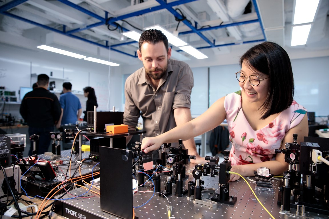 Two researchers working on equipment in the NUS-Singtel lab