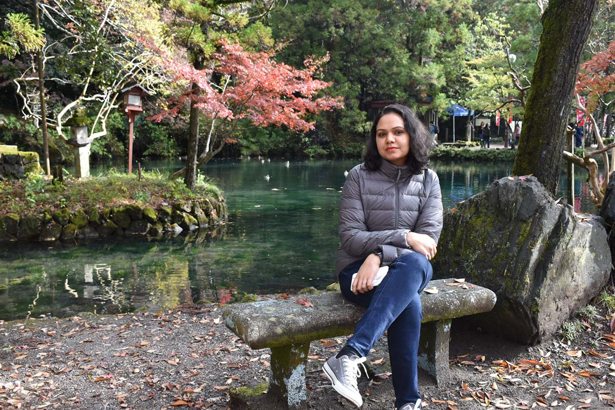 Resmi sits on a stone bench in front of a lake