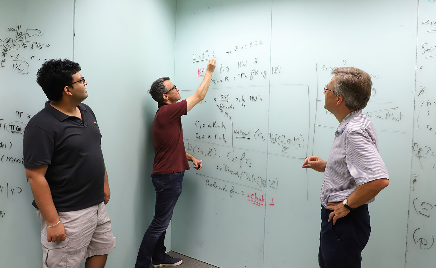 Three researchers at the Centre for Quantum Technologies pictured at a whiteboard with equations