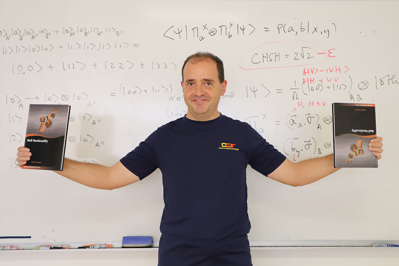 Valerio Scarani with two copies of his book in front of a whiteboard with quantum physics equations